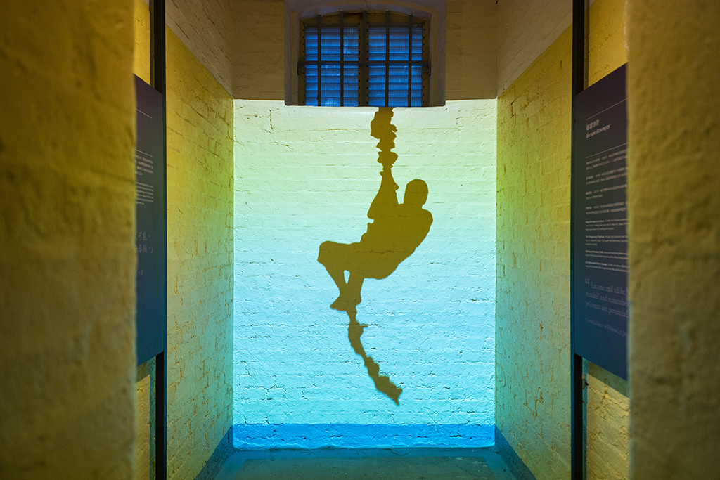 "A projection in a cell shows a depiction of a prisoner attempting an escape from Victoria Prison, a former colonial prison and police station colloquially known as Tai Kwun, or ""big station"", on its opening day to the public in Hong Kong on May 29, 2018. - The multi-million renovation project saw the overhaul of the complex built by the British between the mid-19th and 20th centuries which housed the city's first jail -- Victoria Prison -- as well as its central police station and court buildings. (Photo by Anthony WALLACE / AFP)"