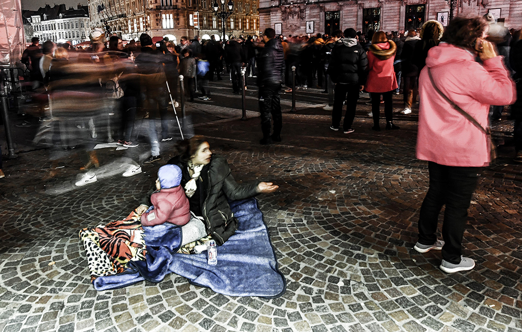 A woman with her child begs in a street of Lille, on March 23, 2018. (Photo by PHILIPPE HUGUEN / AFP)