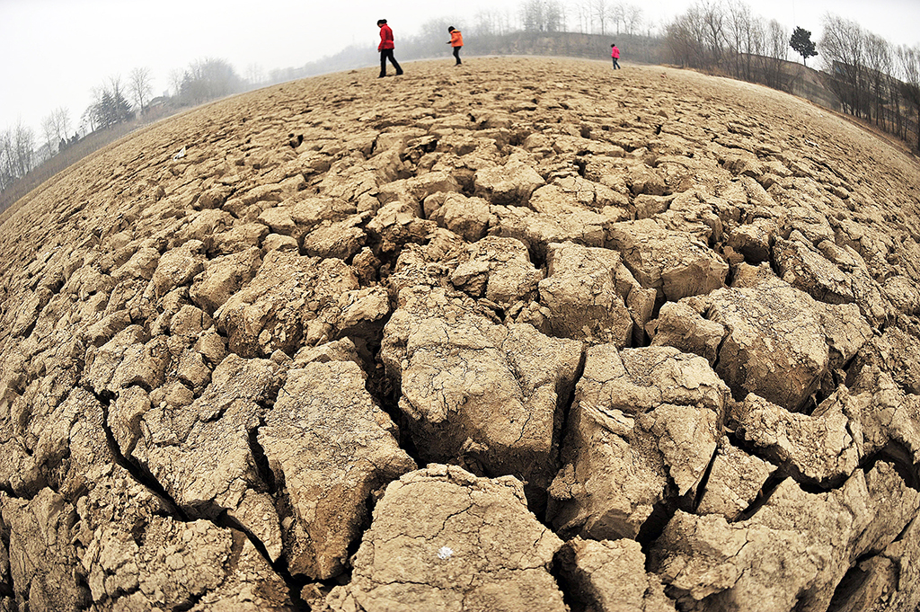 A fisheye lens view of people walking across the dried-up Hubei lake in Zhengzhou, central China's Henan province on February 12, 2009. In four provinces, Henan, Anhui, Shandong and Shanxi, authorities have declared the highest-level drought emergency, the first time the emergency had ever been raised so high, as some regions had not seen precipitation in more than 100 days. CHINA OUT GETTY OUT AFP PHOTO (Photo by STR / AFP)
