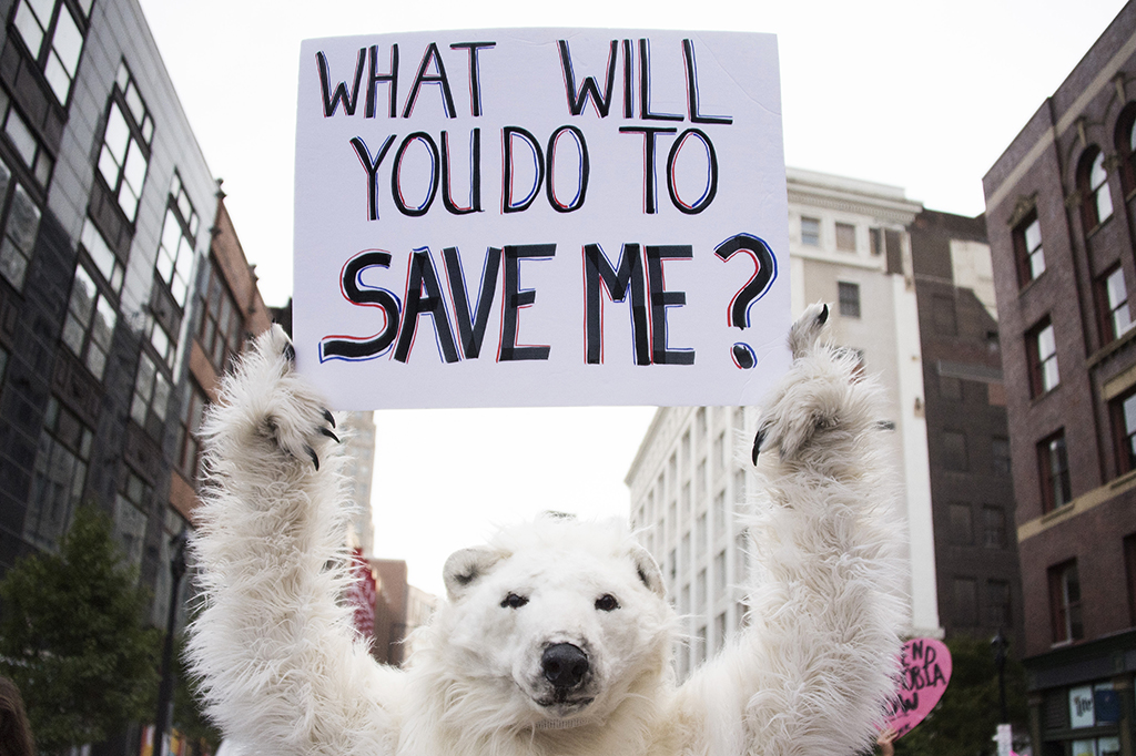 A anti-global warming protester holds up a placard in Cleveland, Ohio, near the Republican National Convention site July 18, 2016. - The Republican Party opened its national convention Monday, kicking off a four-day political jamboree that will anoint billionaire Donald Trump as its presidential nominee. (Photo by JIM WATSON / AFP)