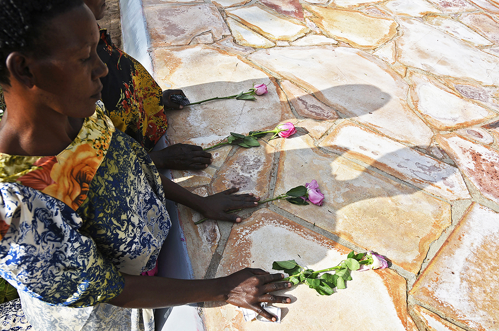 Rwandese refugees lay flowers at Kasensero genocide memorial site in Rakai district on April 21, 2018 during the 24th commemoration of the 1994 genocide against the Tutsi in Rwanda. - 2827 bodies of Rwandese citizens were found on River Kagera in Uganda and buried at this site. (Photo by ISAAC KASAMANI / AFP)