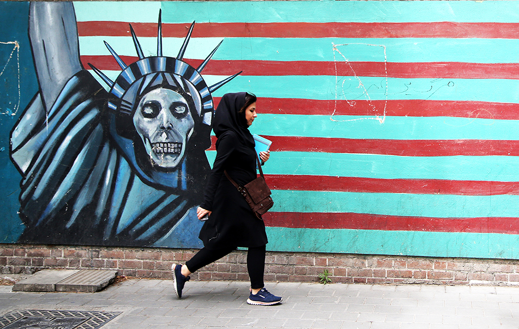 TEHRAN, IRAN - MAY 9 : A woman pasts a mural painted on the wall of the former U.S. Embassy in Tehran, Iran, on May 9, 2018. US President Donald Trump announced 'withdrawal' from Iran nuclear deal on May 9, 2018. Fatemeh Bahrami / Anadolu Agency