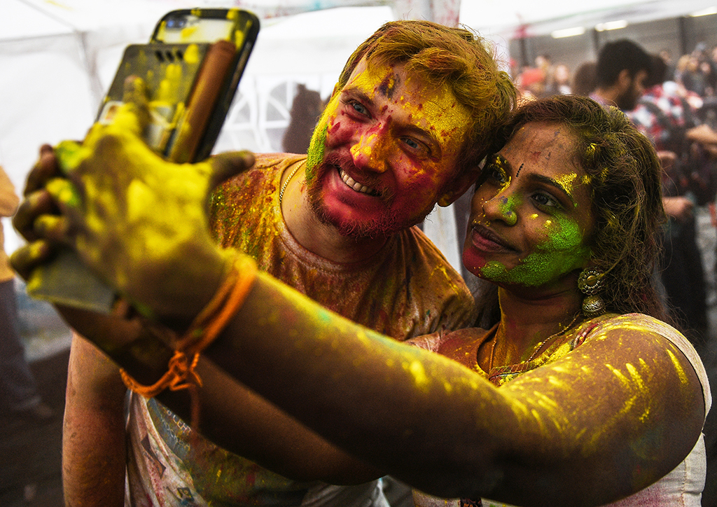 "5827950 24.03.2019 People smeared in coloured powder take a selfie during celebrations of the Holi festival at the Indian Culture Centre in Moscow, Russia. Celebrating Holi, also known as the ""festival of colors"", Hindu people mark the beginning of spring and believe it is a time to enjoy spring's abundant colours. The festival has become popular all around the world. Vladimir Astapkovich / Sputnik"
