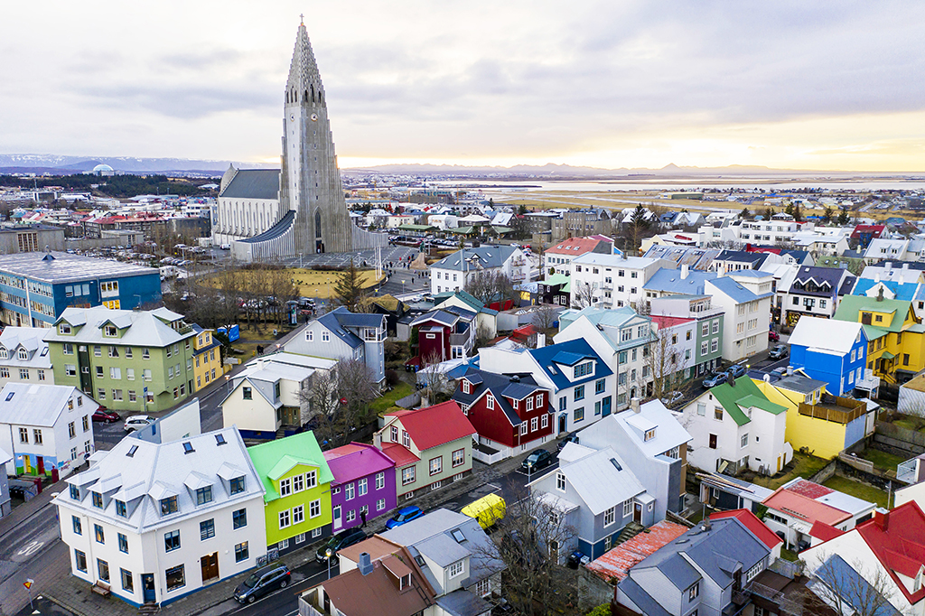 Wide landscape views of buildings, cars, people, homes, apartments, mountains, streets, water, and businesses are seen in Reykjavik, Iceland on December 18, 2018. The Hallgrimskirkja church is predominately centered in the capital, which is the largest city of the island of Iceland. (Photo by Patrick Gorski/NurPhoto)