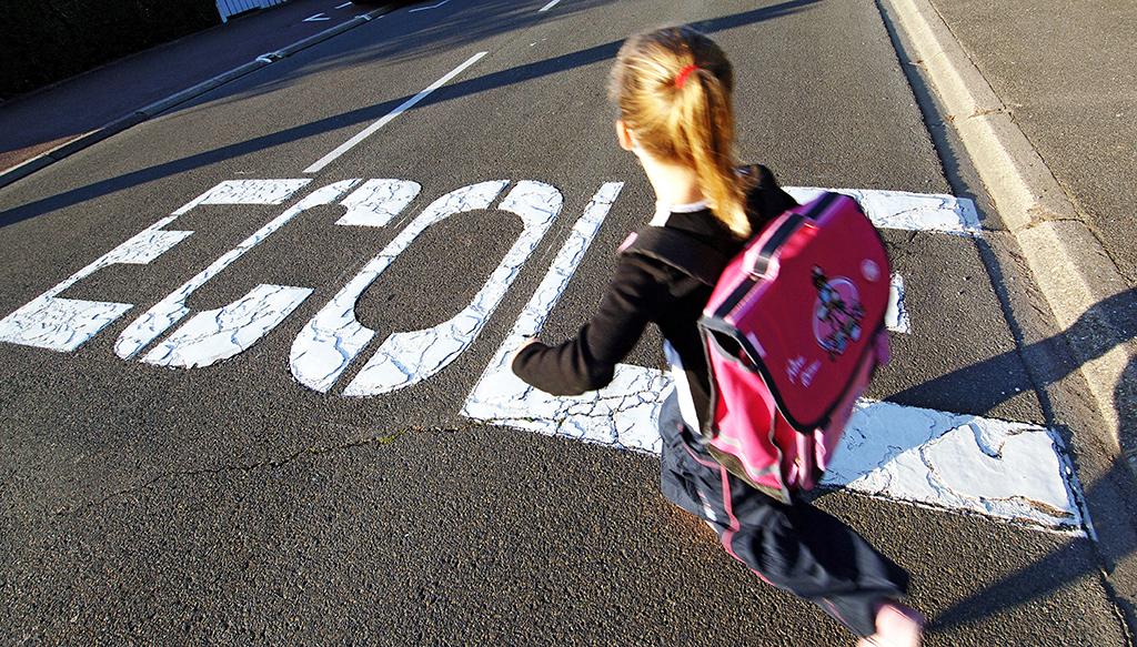une écolière se dirige, le 29 août 2005 vers son établissement scolaire à Hérouville-Saint-Clair, pour sa rentrée scolaire, anticipée en raison de la semaine de quatre jours observée dans la commune depuis quelques années. AFP PHOTO MYCHELE DANIAU (Photo by MYCHELE DANIAU / AFP)