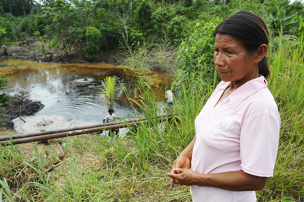 Maria Aguinda (R) looks at the 30-year old oil spillage from the Auca Sur 1 oil well --operated by US Chevron Texaco in the seventies-- at the Rumipamba commune, in the province of Orellana, Amazonia, on February 20, 2011. Last week, a judge from the Sucumbios Provincial Court ordered US giant Chevron to pay USD 9,5 billion in compensation for environmental damages in the Ecuadorean Amazonia. AFP PHOTO/Rodrigo BUENDIA (Photo by RODRIGO BUENDIA / AFP)