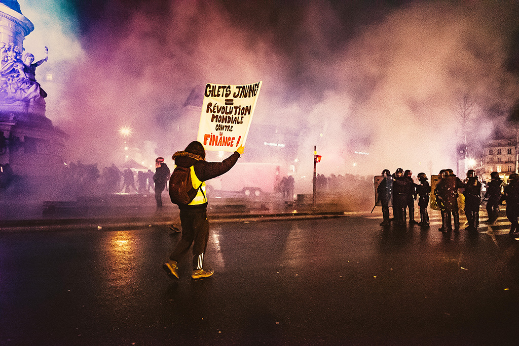 "Intensive intervention of the police forces after launched of tear gas to empty the Republic Square of its protesters, a man holds up a sign ""WORLD REVOLUTION AGAINST FINANCE"". Act 11 of the ""Yellow Vests"" saw born a new approach of the social protest, by taking again the codes of ""Nuit Debout"" (2016) by a nocturnal mobilization supposed to allow the dialogue but cut short last night by the massive intervention of the police. January 26, 2019 - Paris, France. Intervention intensive des forces de l ordre qui viennent de lancer des gaz lacrymogenes pour vider la Place de la Republique de ses manifestants, un homme brandit une pancarte ""REVOLUTION MONDIALE CONTRE LA FINANCE"". L acte 11 des Gilets Jaunes a vu naitre une nouvelle approche de la contestation sociale, en reprenant les codes de Nuit Debout (2016) par une mobilisation nocturne censée permettre le dialogue mais ecourtée hier soir par l'intervention massive des forces de l'ordre. 26 Janvier 2019 - Paris, France."