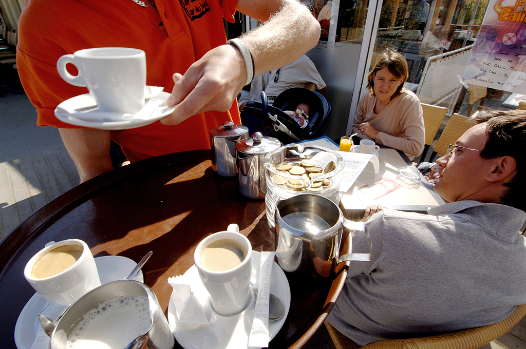 TRAVAIL SAISONNIER - Un serveur, travailleur saisonnier apporte leur café à des clients, le 10 août 2005 à Deauville. AFP PHOTO MYCHELE DANIAU (Photo by MYCHELE DANIAU / AFP)