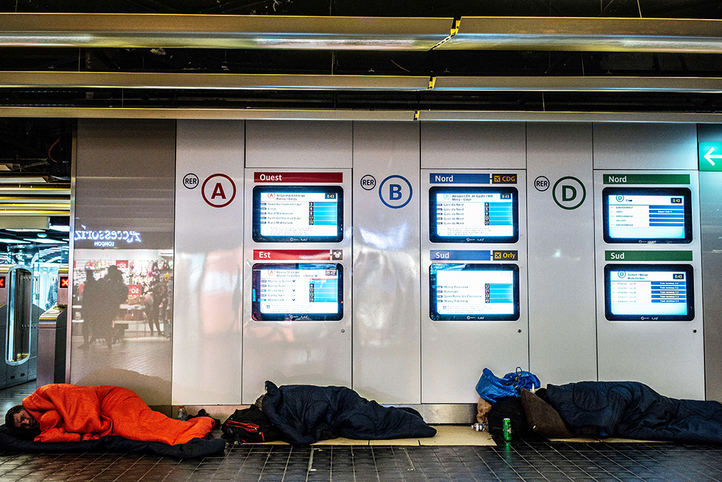 Homeless people sleep at Les Halles suburban train station in Paris, on January 10, 2020, on the 37th day of a strike of French state rail company SNCF and Paris public transports operator RATP employees over the French government's plan to overhaul the country's retirement system. (Photo by Martin BUREAU / AFP)