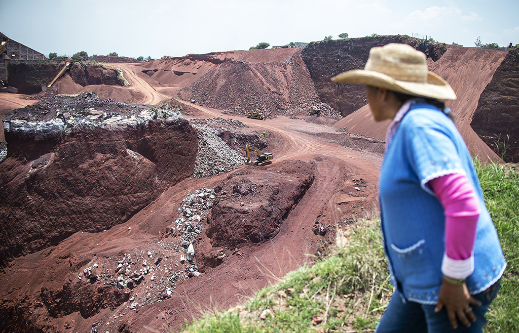 Activist Angelica Maria Gonzalez looks at El Tezoyo quarry -where tezontle and other stones are extracted for the construction of the new international airport of Mexico City- in La Concepcion village, Tezoyuca municipality, Mexico State, Mexico, on July 31, 2018. - Residents demand the closure of the quarry since the constant detonation of rocks is causing damage in nearby houses. (Photo by Pedro PARDO / AFP)