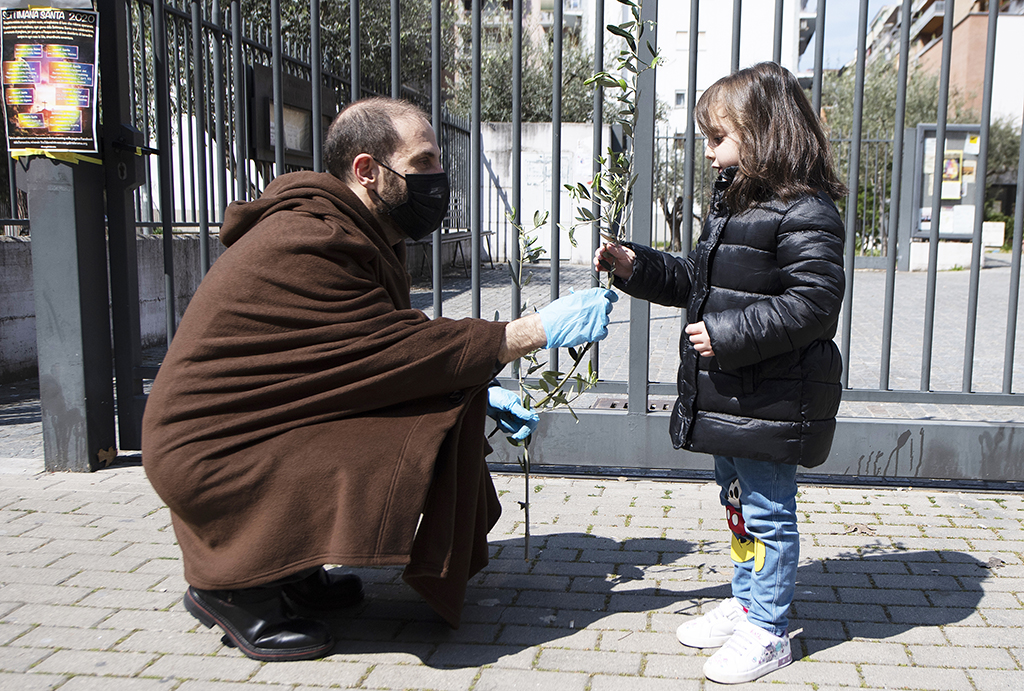 Parish priest Don Antonio Lauri (L) hands a palm branch to a girl after celebrating Palm Sunday mass from the rooftop of the San Gabriele dell'Addolorata church in Rome on April 5, 2020, during the country's lockdown aimed at curbing the spread of the COVID-19 infection, caused by the novel coronavirus. (Photo by Tiziana FABI / AFP)