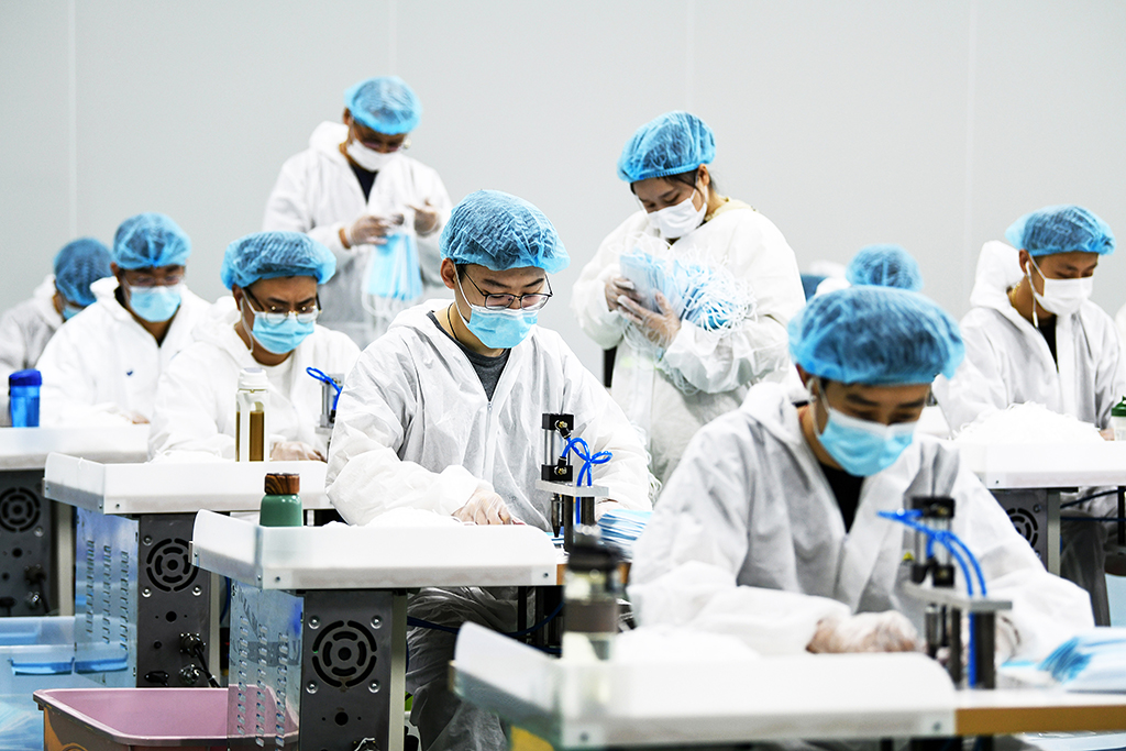 This photo taken on April 8, 2020 shows workers producing face masks that will be exported at a factory in Nanchang in China's central Jiangxi province. (Photo by STR / AFP) / China OUT