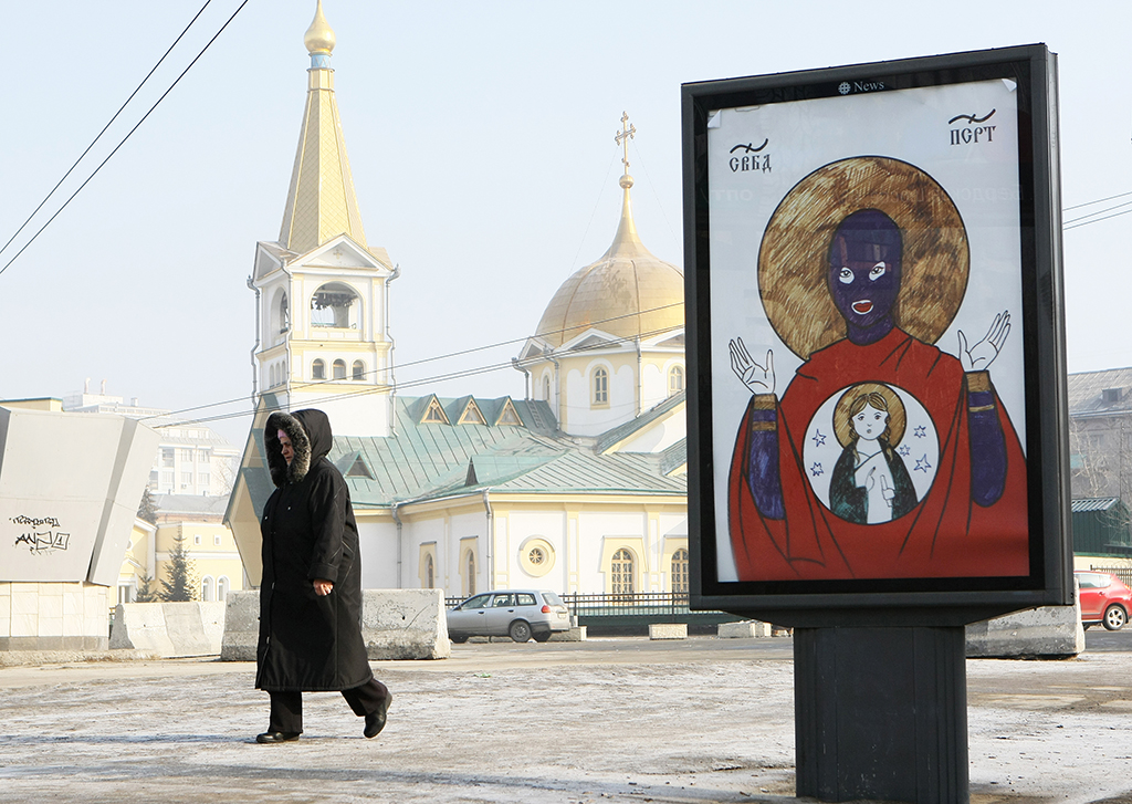 1063080 Russia, Novosibirsk. 03/12/2012 A woman passing by a billboard stylized as an icon in support of the members of the Pussy Riot punk group at the Ascension Cathedral in Novosibirsk. Alexandr Kryazhev/Sputnik