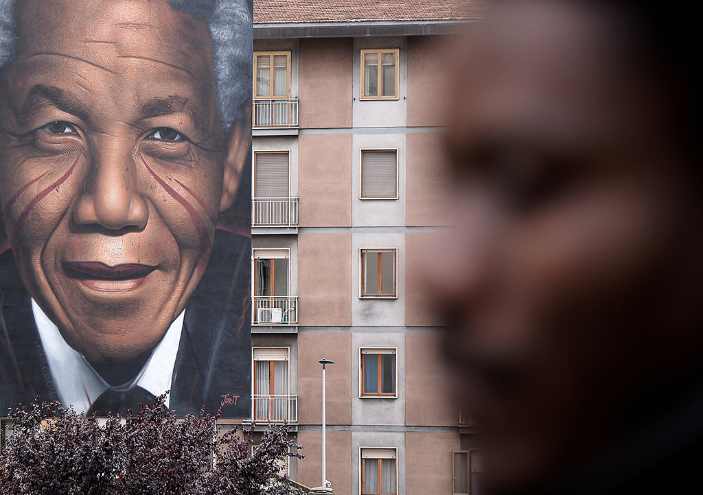 """A pedestrian walks by a mural by Italian street artist Jorit Agoch, entitlied """"Il Condominio dei Diritti"""" (The Condominium of Rights), and depicting late former South African president and peace icon Nelson Mandela on Demceber 1, 2019, in Florence. - The 125 square metres artwork in tribute the Nobel Peace Prize winner was created on a wall of a 4 storey public housing building at the Piazza Leopoldo in Florence. (Photo by Filippo MONTEFORTE / AFP) / RESTRICTED TO EDITORIAL USE - MANDATORY MENTION OF THE ARTIST UPON PUBLICATION - TO ILLUSTRATE THE EVENT AS SPECIFIED IN THE CAPTION"""