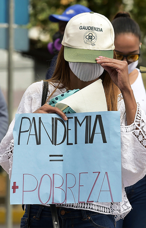 "A sex worker holds a sign reading ""Pandemic = Poverty"" during a protest in Quito on July 6, 2020, amid the new coronavirus pandemic. - Hundreds of sex workers and nightclub workers demanded the government the reopening of their work places, closed since the beginning of March. (Photo by RODRIGO BUENDIA / AFP)"
