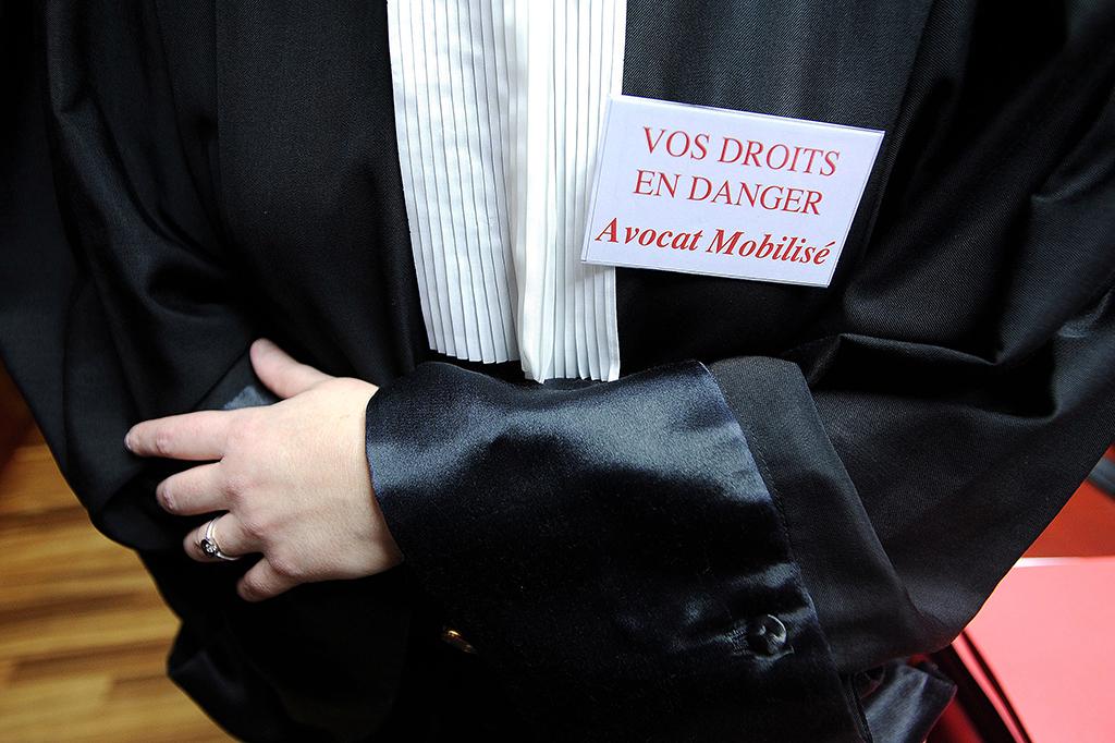 """Une avocate porte un badge sur lequel est inscrit """"Vos droits en danger"""" le 04 février 2011 au Palais de Justice de Nantes, en réaction aux dernières mises en cause de la justice et de la police par le président Nicolas Sarkozy dans l'affaire Laetitia. Après avoir voté la veille """"une semaine sans audience"""", les syndicats de la magistrature menacent d'organiser une journée nationale d'action le 10 février, avec un rassemblement à Nantes en point d'orgue. AFP PHOTO / JEAN SEBASTIEN EVRARD (Photo by JEAN-SEBASTIEN EVRARD / AFP)"""