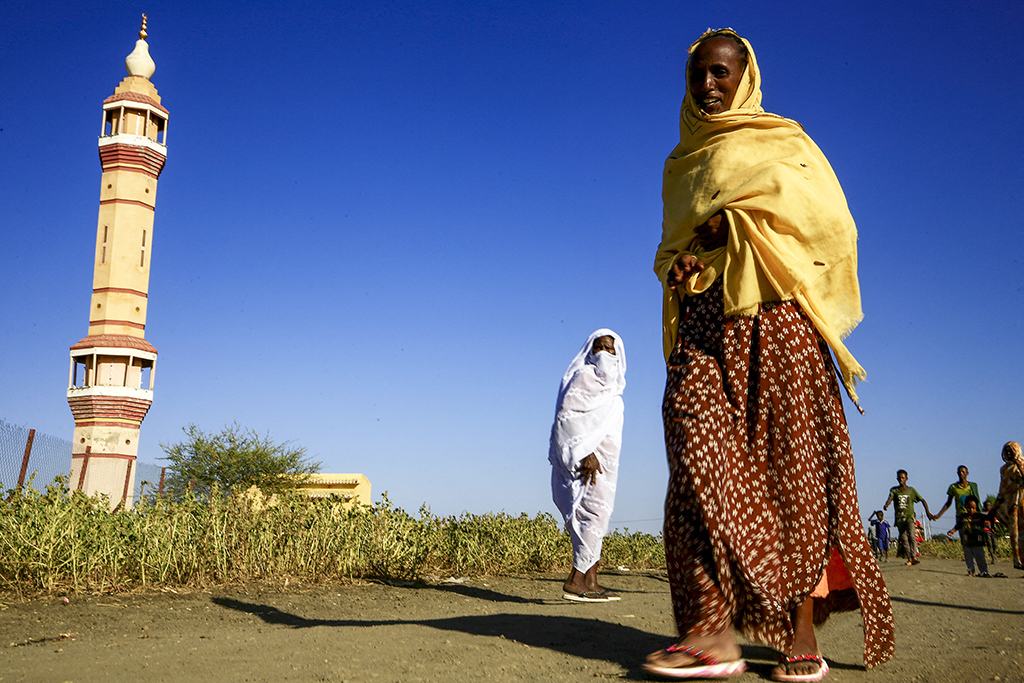 An Ethiopian refugee, who fled the fighting in Tigray Region, walks past a mosque at a border reception centre (Village 8) in Sudan's eastern Gedaref State on November 29, 2020. (Photo by ASHRAF SHAZLY / AFP)