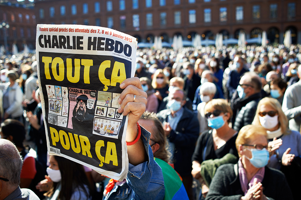 A man brandishes a Charlie Hebdo newspaper reading 'All that for this'. After the killing of Samuel Paty, teacher of Geography-History, in Conflans-Sainte-Honorine (Yvelines) on October 16th several thousands of people gathered on the main square of Toulouse, in front of the townhall, the Capitole, to defend freedom of expression and to pay tribute to Samuel. Some people came with a cover of Charlie Hebdo as the teacher has been killed after showing at his pupils the Charlie Hebdo' caricatures of Muhammed. The killer has been killed by French police afterwards. On October 18th, 2020 in Toulouse, France. (Photo by Alain Pitton/NurPhoto)
