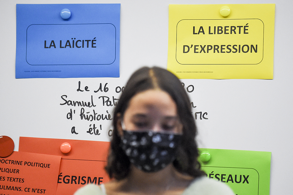 A student observe a minute of silence at the Honore d' Estienne High School in Orves, Carquefou on November 2, 2020, in homage to slain history teacher Samuel Paty, who was beheaded by an attacker for showing pupils cartoons of the Prophet Mohammed in his civics class, on October 19, 2020, in Conflans-Sainte-Honorine, northwest of Paris. - Schoolchildren across France were to observe a minute of silence at 11:00 am (1000 GMT), as students returned to classes after the autumn break, to remember Samuel Paty, 47, who was killed in Conflans-Sainte-Honorine, outside Paris, on October 16 just as the holiday began. Paty had shown his class a cartoon of the prophet Mohammed for a lesson on freedom of expression, spurring an online campaign targeting him. His killing further set France on edge as French president spearheads a campaign against Islamist radicalism. (Photo by Sebastien SALOM-GOMIS / AFP)