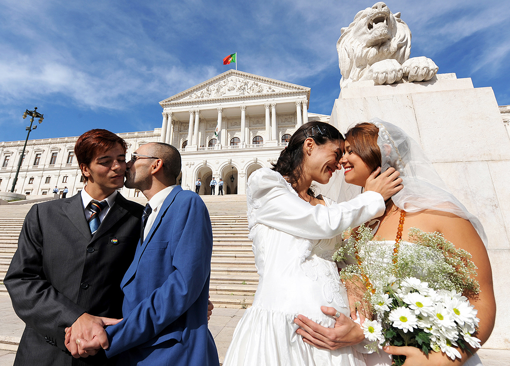 """Gay rights activists """"Jose"""" (L) and """"Manuel"""" (2ndL) and """"Ana"""" (2ndR) and """"Maria"""" (R) stage a wedding ceremony in front of the Portuguese parliament in downtown Lisbon on October 10, 2008. Left-wing parties Bloco de Esquerda and Os Verdes failled today to pass a bill proposing to legalize gay marriage. AFP PHOTO / FRANCISCO LEONG"""