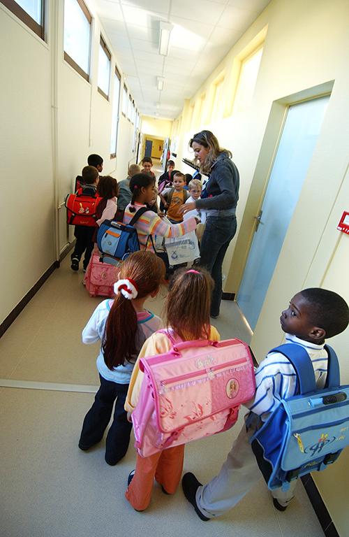 des élèves du groupe scolaire Gringoire à Hérouville Saint-Clair s'apprêtent à regagner leur classe, le 24 août 2004, le jour de leur rentrée scolaire anticipée due à la pratique de la semaine de quatre jours. AFP PHOTO MYCHELE DANIAU